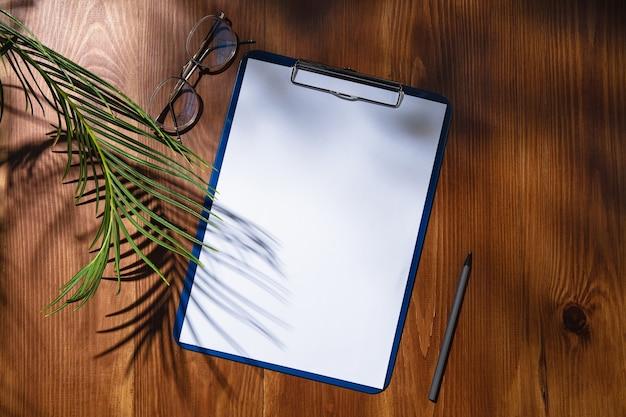 실내 나무 테이블에 시트 및 작업 도구. 홈 오피스의 창의적이고 아늑한 직장, 표면에 식물 그림자로 영감을주는 모의. 원격 사무실, 프리랜서, 분위기의 개념.