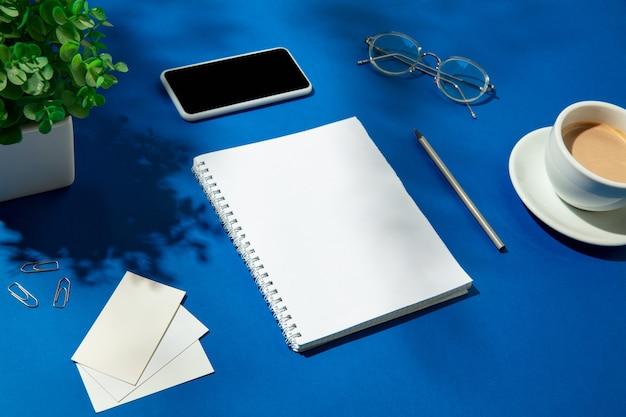 실내 파란색 테이블에 시트, 커피 및 작업 도구. 홈 오피스의 창의적이고 아늑한 직장, 표면에 식물 그림자로 영감을주는 모의. 원격 사무실, 프리랜서, 분위기의 개념.