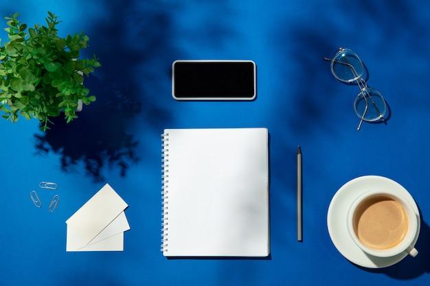 Листы, кофе и рабочие инструменты на синем столе в помещении. креативное, уютное рабочее место в домашнем офисе, вдохновляющий макет с тенями растений на поверхности. концепция удаленного офиса, фриланс, атмосфера.