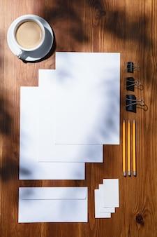 실내 나무 테이블에 시트, 커피 및 작업 도구. 홈 오피스의 창의적이고 아늑한 직장, 표면에 식물 그림자로 영감을주는 모의. 원격 사무실, 프리랜서, 분위기의 개념.