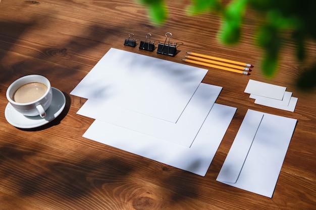 Листы, кофе и рабочие инструменты на деревянном столе в помещении.
