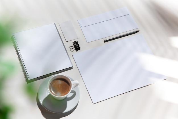 Листы, кофе, рабочие инструменты на белом столе в помещении.