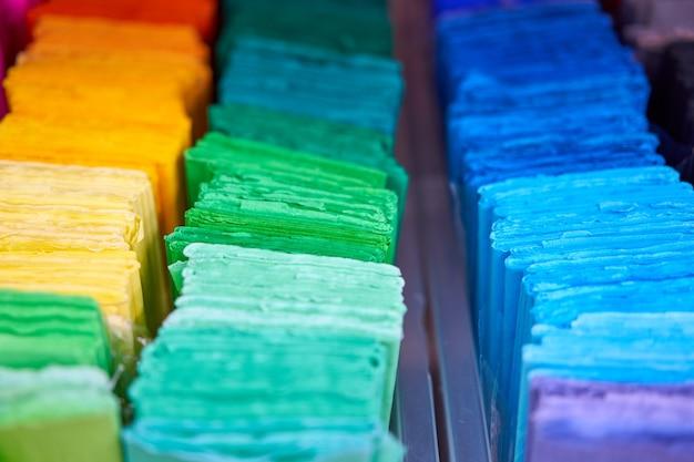 デザイナーの創造的な作品のためのシート色の段ボール。色とりどりの画用紙を店内に積み上げます。販売文房具店の棚にカラフルなアートペーパー