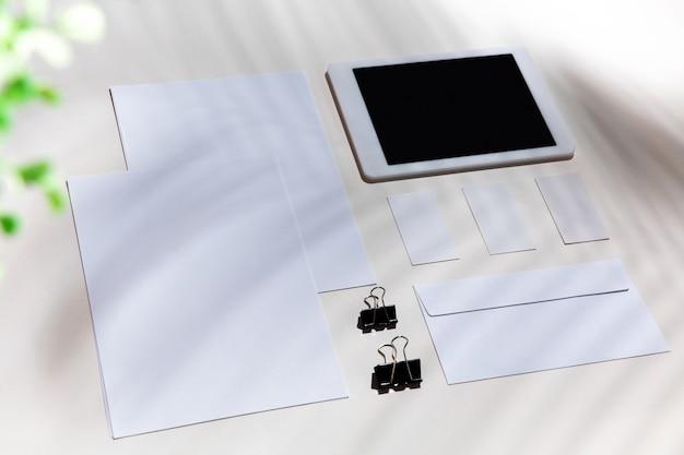 실내 흰색 테이블에 시트, 가제트 및 작업 도구. 홈 오피스의 창의적이고 아늑한 직장, 표면에 식물 그림자로 영감을주는 모의. 원격 사무실, 프리랜서, 분위기의 개념.