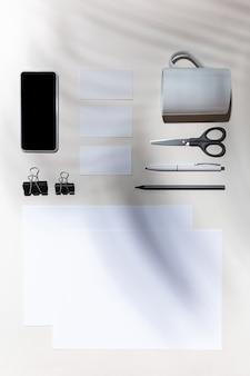 Листы, гаджеты и рабочие инструменты на белом столе в помещении.