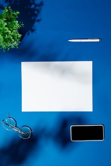 Sheets, gadgets and work tools on a blue table indoors. creative, cozy workplace at home office, inspirational mock up with plant shadows on surface. concept of remote office, freelance, atmosphere.