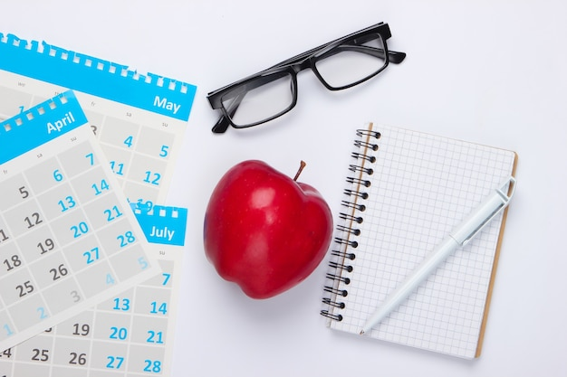 Sheets of the monthly calendar, red apple, glasses, notebook on white. economic calculation, costing