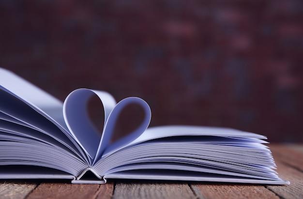 Листы книги изогнуты в форме сердца на несфокусированном фоне