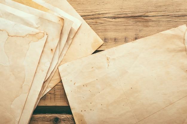Листы старой винтажной бумаги на деревянном столе. скопируйте пространство. фото высокого качества