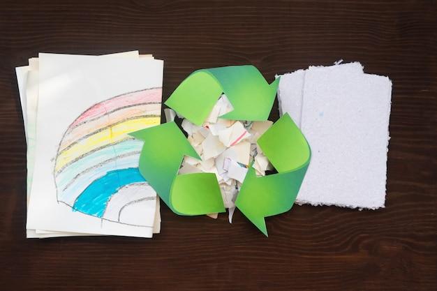 紙のシートとゼロウェイストサインがテーブルの上にあります。紙のリサイクルの概念。
