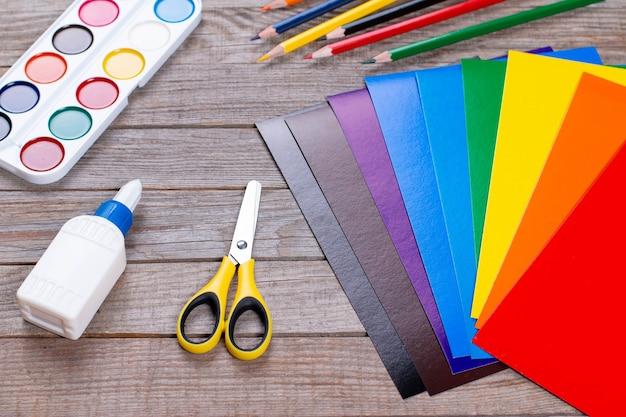 木製のテーブルに紙、接着剤、はさみのシート。子供向けの工芸品、子供向けアートプロジェクト。子供のためのクラフト。