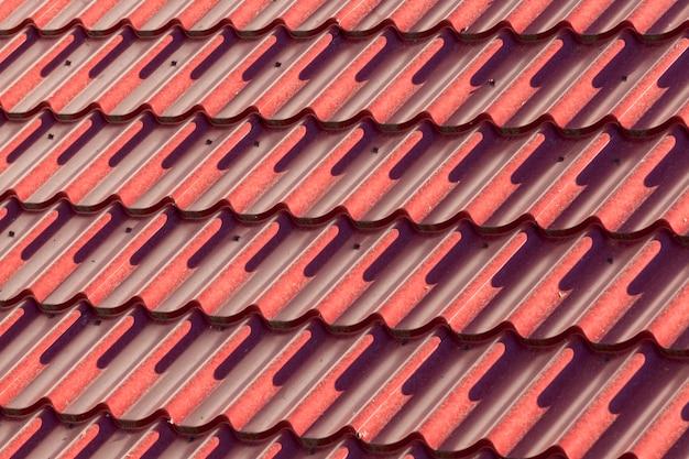 고르지 않은 붉은 금속 지붕 시트. 화창한 날에 근접