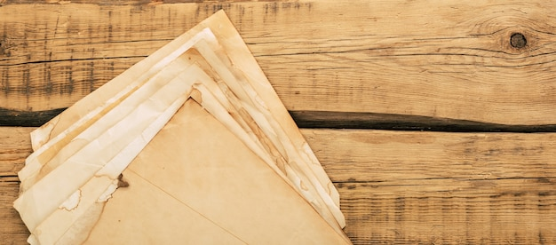 Sheets of old vintage paper on a wooden table. copy space. high quality photo
