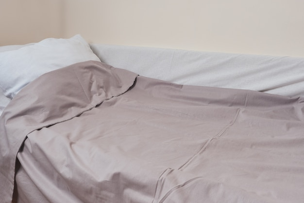 Sheets and pillow, bed made for sleeping