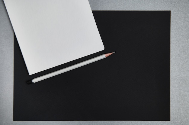 Sheets of white and black paper and gray wooden pencil. black and white still life. flat lay . top view.