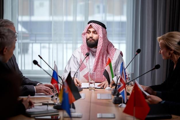 Человек шейха представляет свои идеи коллегам и слушает идеи для успешных инвестиций в ярком современном офисе, сидя за микрофоном.