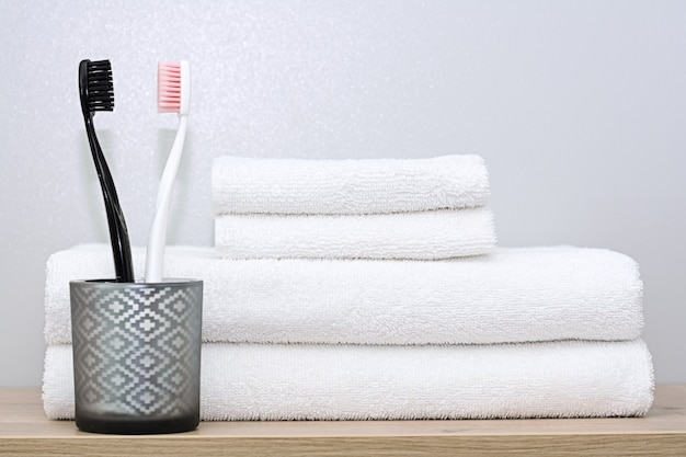 On a shelf in the bathroom are white towels of various sizes neatly folded and a glass cup with black and pink toothbrushes. the concept of morning procedures, order home, family.