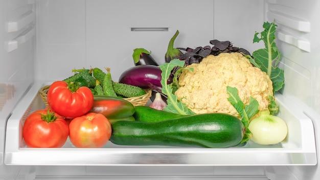 Полка в холодильнике с овощами.