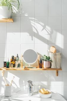 無駄のない化粧品と再利用可能なボトルを備えた白いモダンなバスルームの棚。壁の影。ウェルネスと持続可能性の概念