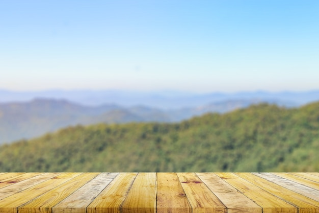 Полка из коричневой деревянной доски с размытой зеленой природой