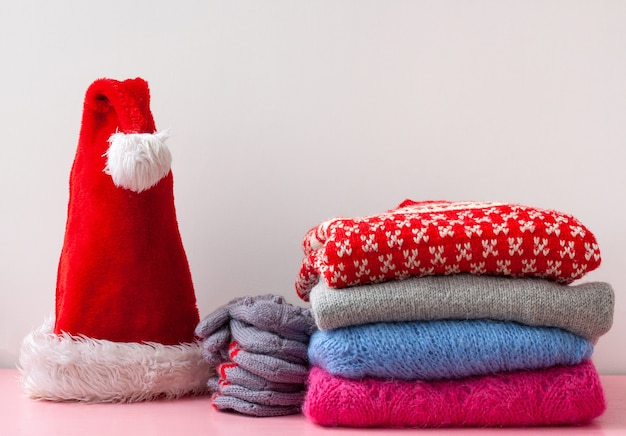 On the shelf next to a stack of christmas and new year sweaters is a stack of mittens and a santa claus hat.
