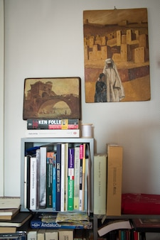 A shelf with books on a white wall and two paintings with architectural images in a small apartment