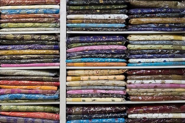 화려한 옷이 있는 선반. 인도 국가 의상. sari는 선반 위에 있는 가게에 있어요. 여성 사리. 뉴델리 인도 메인 바자회