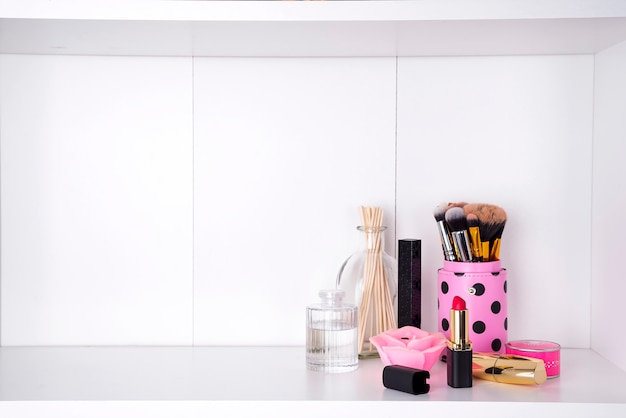 Shelf with cosmetics in bathroom on a white bathroom shelf
