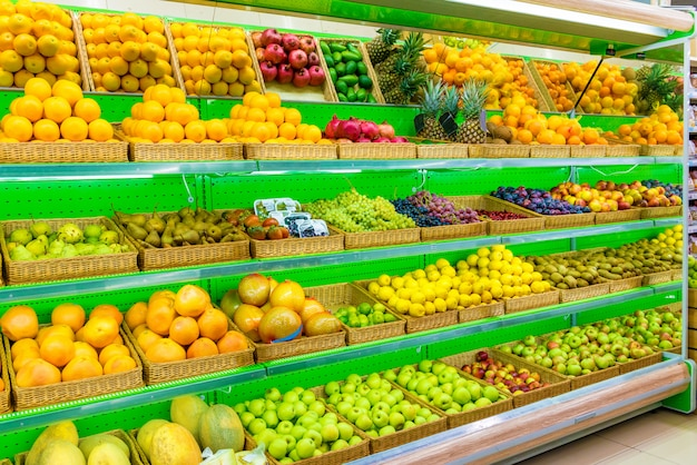 Shelf with fresh organic fruits on a farm market supermarket. apple, orange, grapes, persimmon, kiwi, pineapple, pear, plum, prunes, melon, watermelon, exotic fruit.