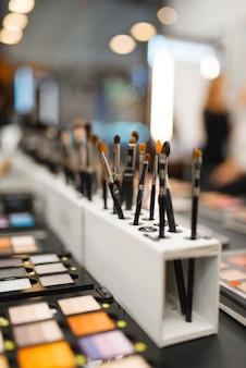 Полка с тенями и кистями в магазине косметики, никто. роскошный салон красоты, витрина с продуктами на модном рынке