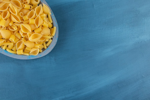 Shell uncooked pasta in a board on a dark-blue background.