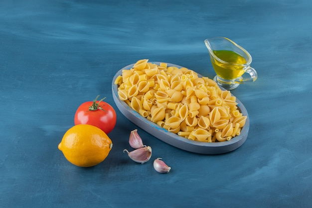 Shell pasta cruda in una tavola su uno sfondo blu scuro.