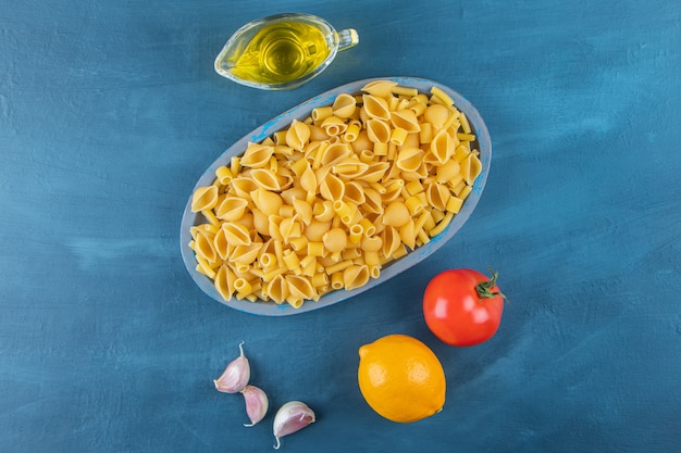 Sgusciare la pasta cruda in un tagliere con pomodoro rosso fresco e aglio.