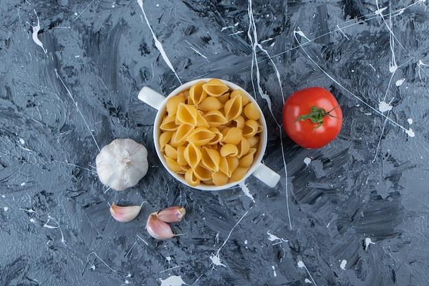 Shell pasta cruda in una ciotola con pomodori rossi freschi e aglio.