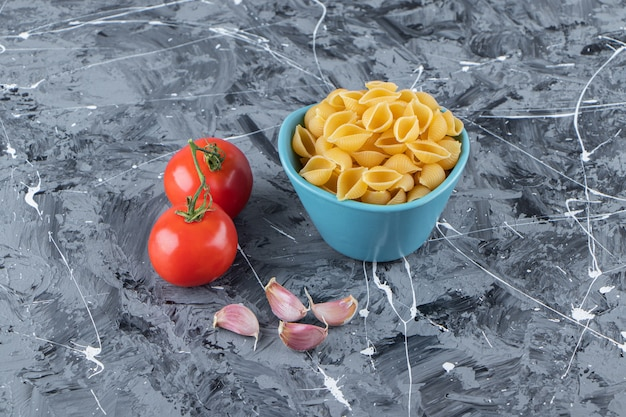 Sgusciare la pasta cruda in una ciotola con pomodori rossi freschi e aglio.