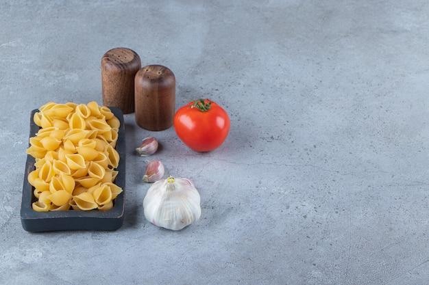 신선한 빨간 토마토와 마늘을 곁들인 보드에 요리하지 않은 파스타를 껍질을 벗기십시오.