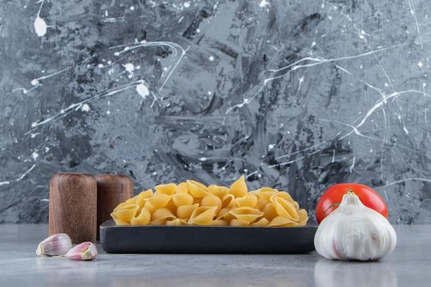 Выложите сырые макароны на доске со свежими красными помидорами и чесноком.