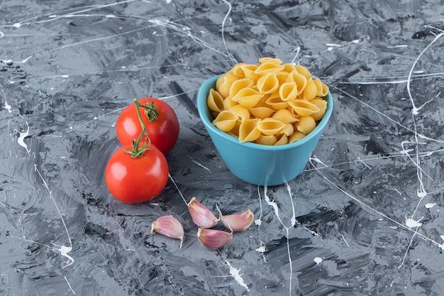Выложите сырые макароны в миску со свежими красными помидорами и чесноком.