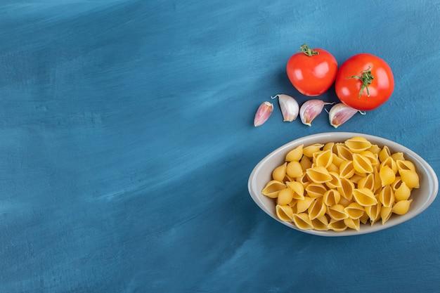 신선한 빨간 토마토와 마늘과 함께 그릇에 요리하지 않은 파스타를 껍질을 벗기십시오.