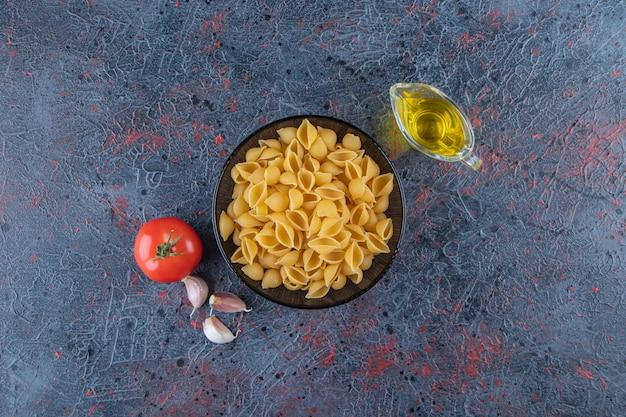 Выложите сырые макароны в стеклянной миске со свежими красными помидорами и чесноком.