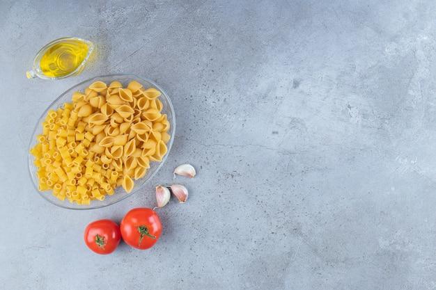 Guscio la pasta cruda con i ditali rigati crudi secchi in una ciotola di vetro con pomodori rossi freschi e aglio.