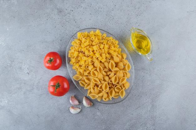 Sgusciare la pasta cruda con ditali rigati secchi crudi in una ciotola di vetro con pomodori rossi freschi e aglio.