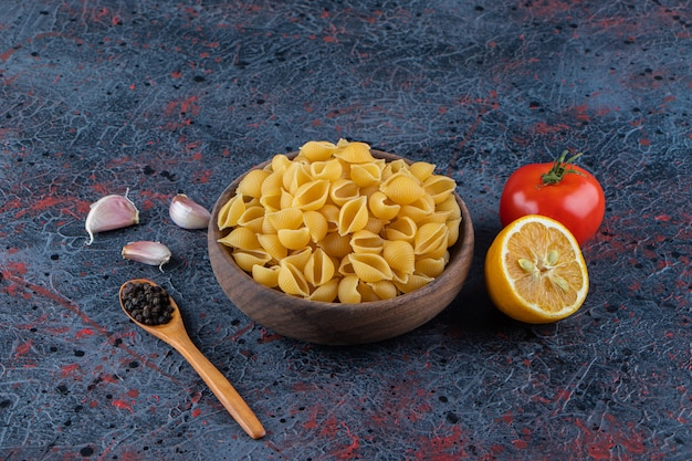 Shell uncooked pasta in a wooden bowl with fresh red tomato and sliced lemon .