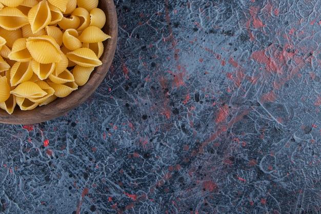 Shell pasta cruda in una ciotola di legno con pepe in grani su uno sfondo scuro.