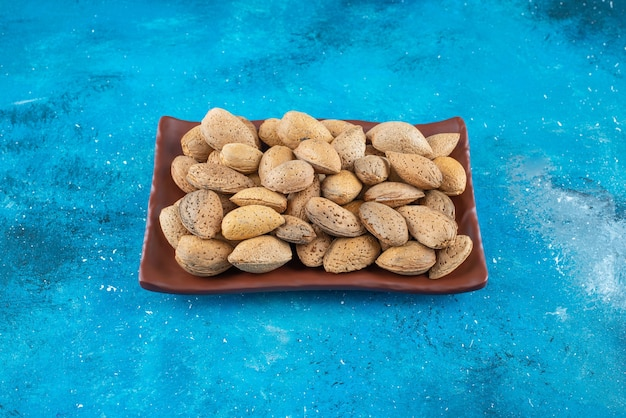 Shelled almonds in a plate on the blue surface