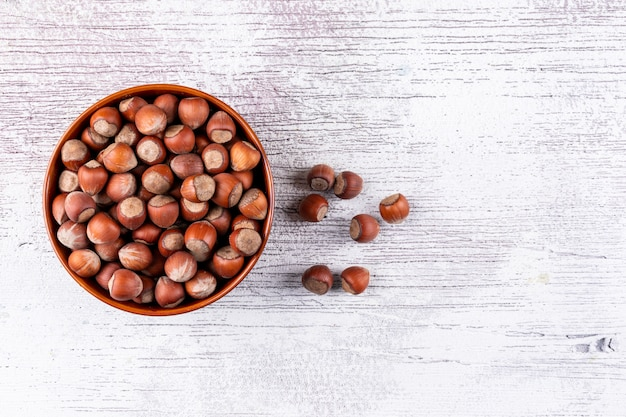 Shelled hazelnuts in a bowl on a white wooden table. top view.