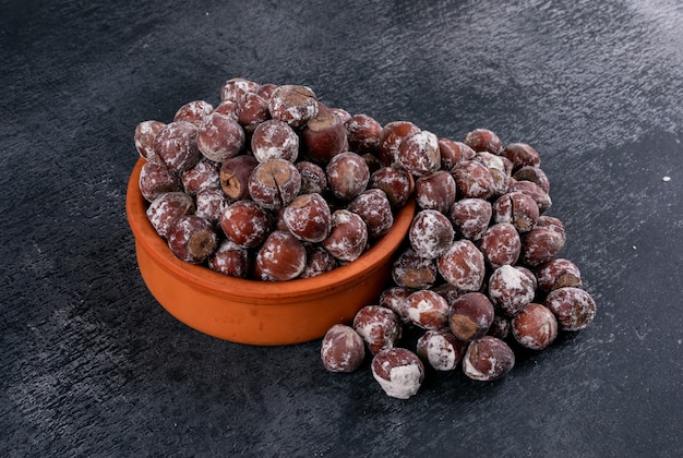 Shelled hazelnuts in a brown bowl on a dark stone table. high angle view.