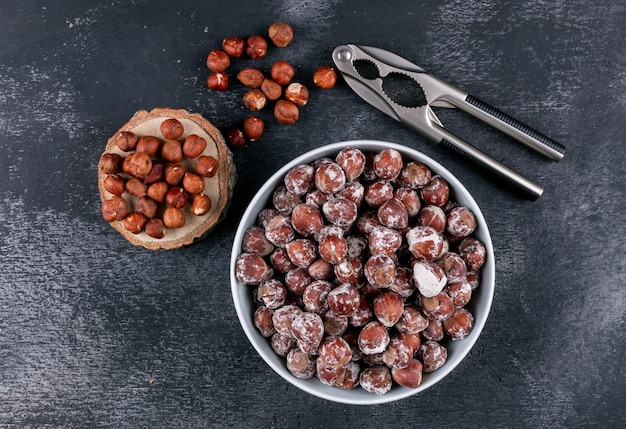 Shelled hazelnuts in a white bowl with piece of wood top view on a dark stone table