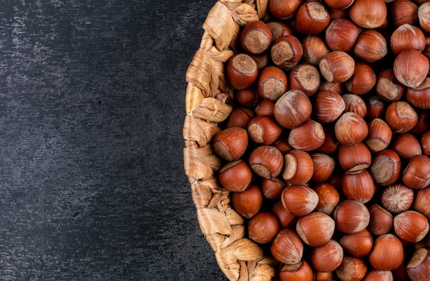 Shelled hazelnuts in a wicker basket on a black stone table. close-up.
