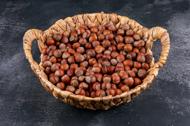 Shelled hazelnuts in a wicker basket on a dark stone table. high angle view.